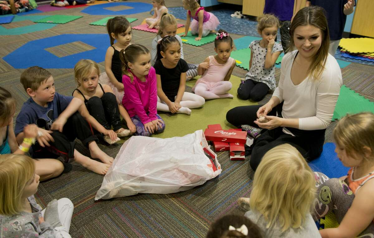 Meghan Swain, with Midland Festival Ballet, hands out ballet shoes 03/12/18 at the Centennial Branch Library, for Princess Ballet Camp during Spring Break week. Tim Fischer/Reporter-Telegram