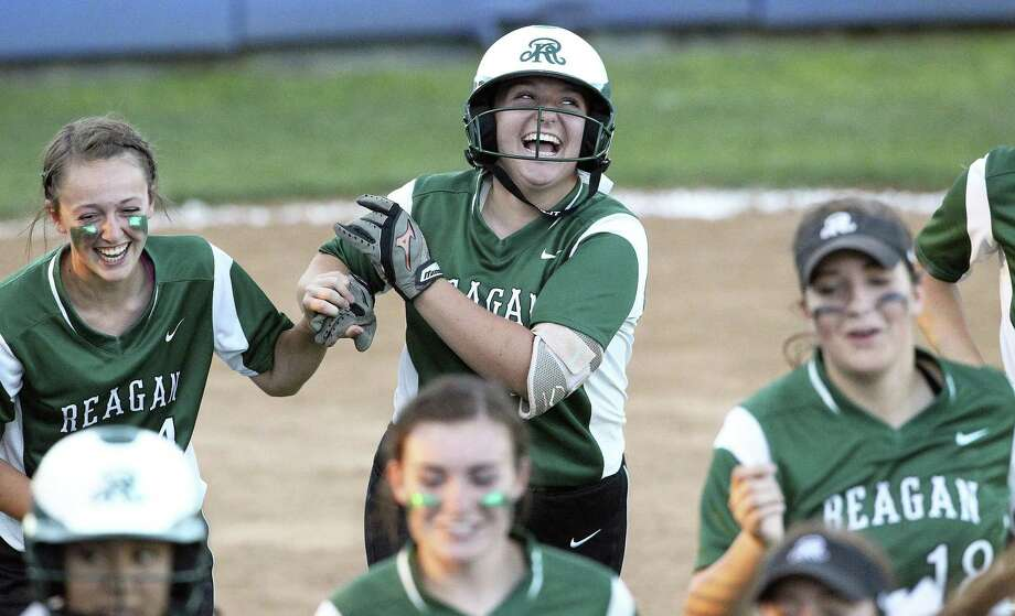 Kamryn Caldwell (center) celebrates with teammates after a solo homer starts the Rattler scoring as Reagan plays Brennan in game 1 of a best of three 6A second round softball playoff game at SAISD Complex on May 6, 2016. Photo: TOM REEL, STAFF / SAN ANTONIO EXPRESS-NEWS / 2016 SAN ANTONIO EXPRESS-NEWS