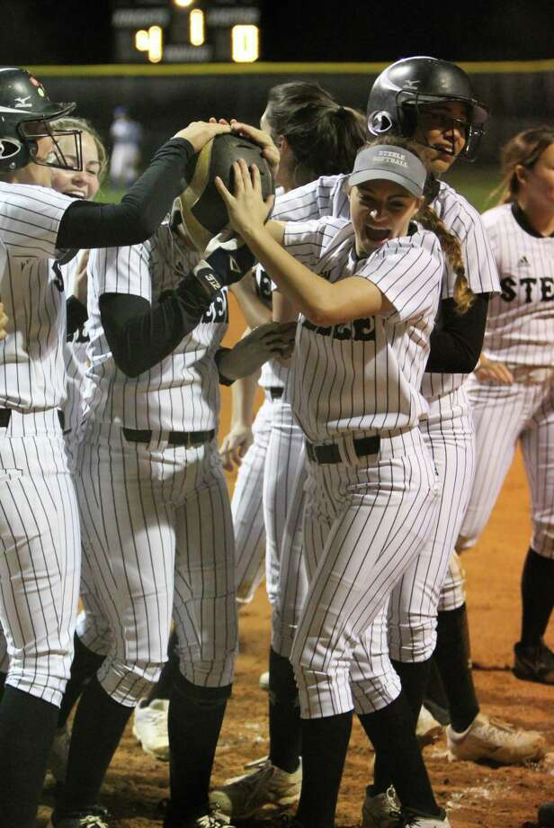 Steele pitcher Sara Papizan (wearing batting helmet) is mugged by her teammates after her three-run home run in the first inning of Friday's 7-1 win over New Braunfels. Photo: Greg Bell / For The NE Herald