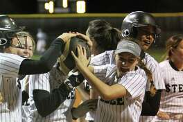 Steele pitcher Sara Papizan (wearing batting helmet) is mugged by her teammates after her three-run home run in the first inning of Friday's 7-1 win over New Braunfels.