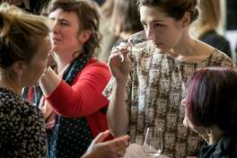 People enjoy wines at a natural wine tasting in the Starline Social Club in Oakland, Calif. on March 11th, 2018.
