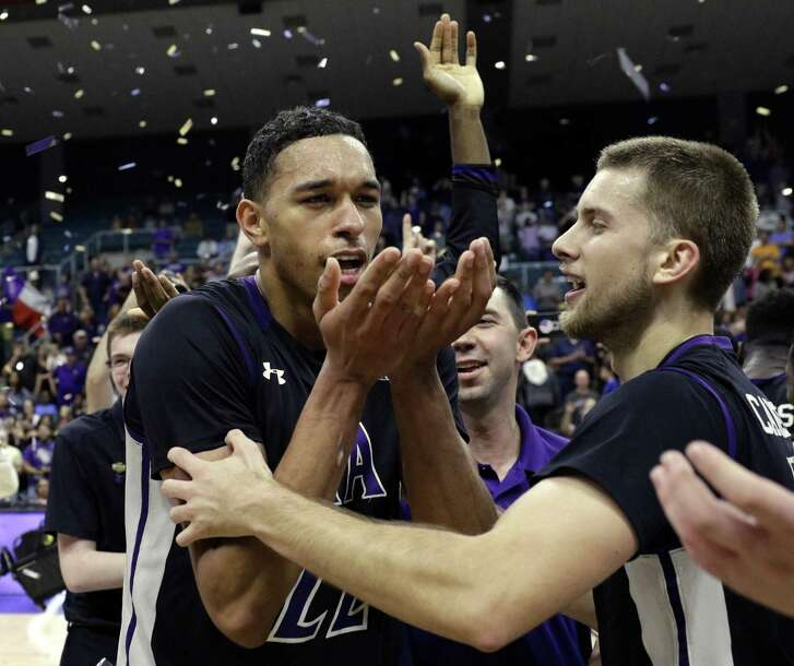 Stephen F. Austin forward TJ Holyfield (22) blows away falling confetti as John Comeaux (10) reaches for a hug after defeating Southeastern Louisiana after an NCAA college basketball game in the Southland Conference's Men's Basketball Tournament Championship Saturday, March 10, 2018, in Houston. (AP Photo/Michael Wyke)