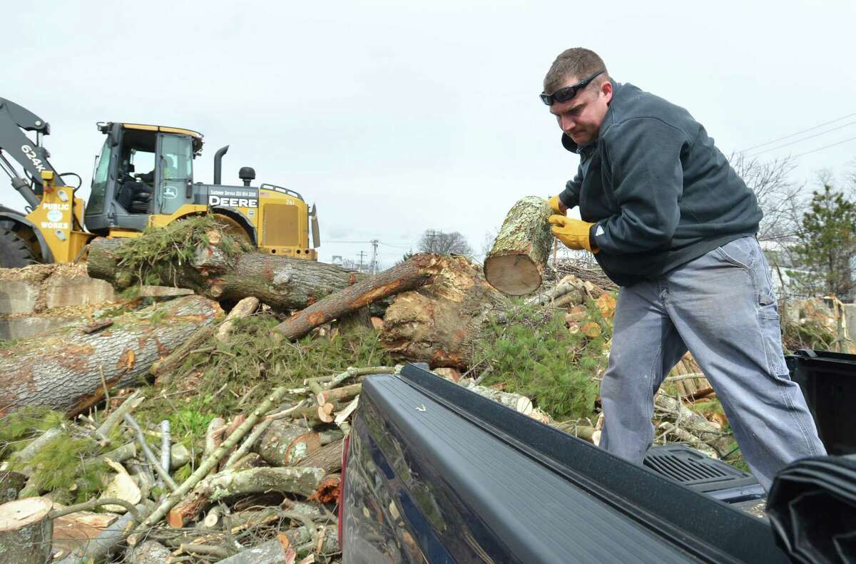 Daniel Byrne pulls logs and branches from his truck after clearing downed trees from his Field Street home, and unloads them at the yard waste area at the Department of Public Works in Norwalk on Monday.