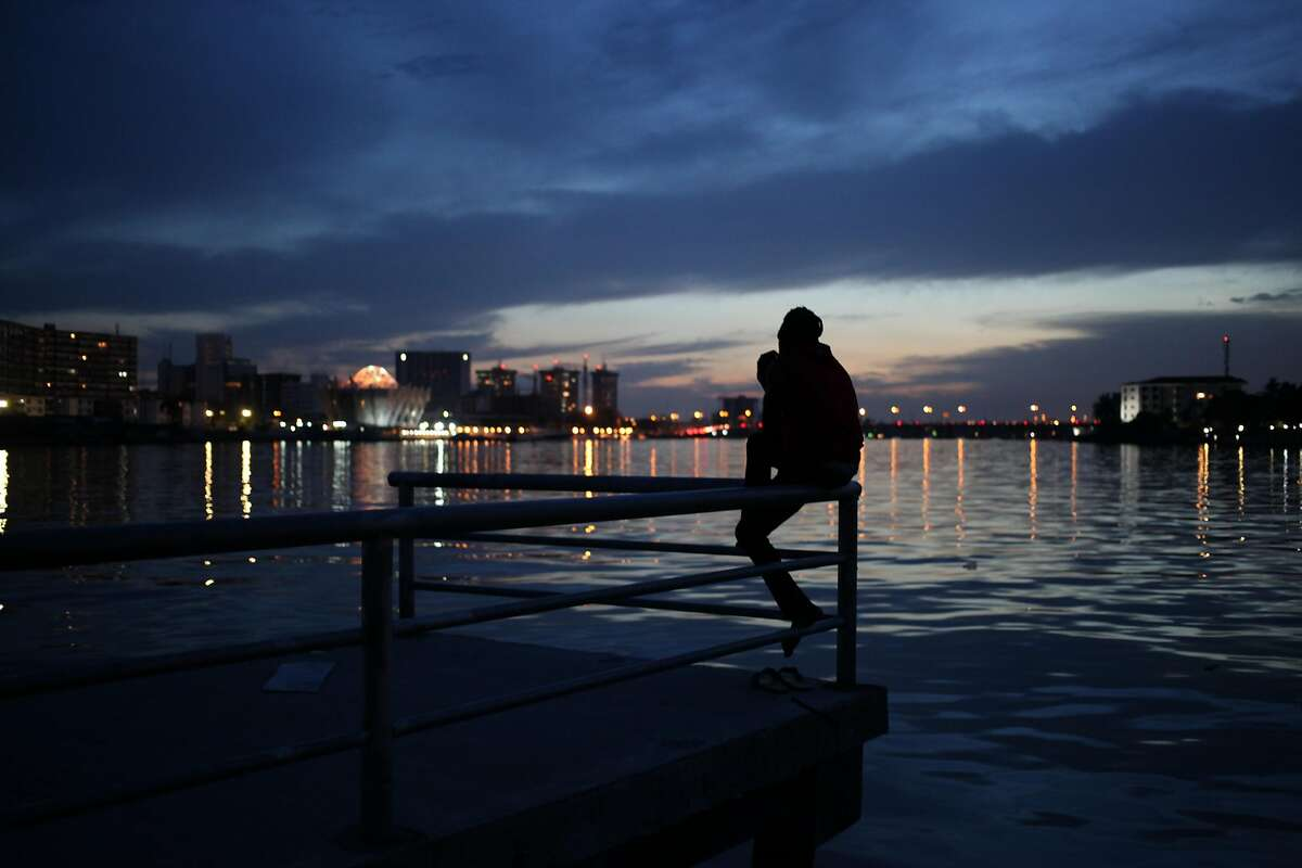 A man watches the sunset over the Lagos Lagoon in Lagos, Nigeria, on Monday, April 15, 2013. (AP Photo/Jon Gambrell)
