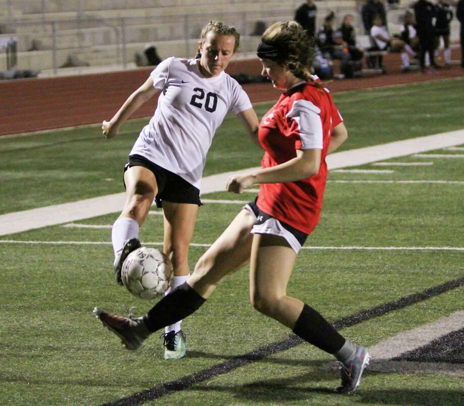 Steele Lady Knight Hannah Smith (20) battles for the ball with a New Braunfels Canyon Cougarette during Steele's 2-0 loss Friday to Canyon. Photo: Greg Bell / For The NE Herald