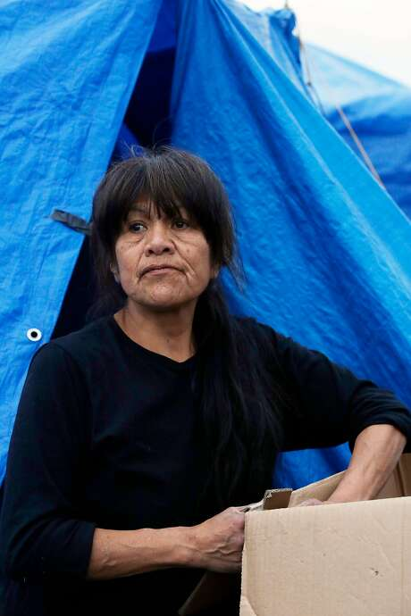 Tesla Meyer breaks down cardboard boxes to lay on top of pallets under her bedding in her tent at Last Chance. Photo: Lea Suzuki, The Chronicle