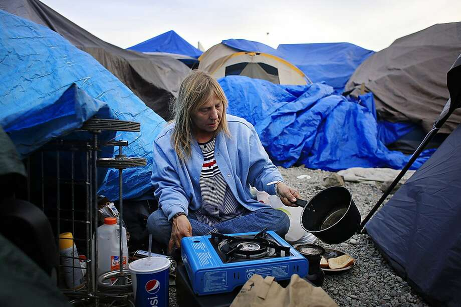 Samantha Howell makes coffee as she prepares dinner at Last Chance, a tent encampment in the Roseland area of south Santa Rosa. The population in tent camps quadrupled after the wildfires. Photo: Lea Suzuki, The Chronicle