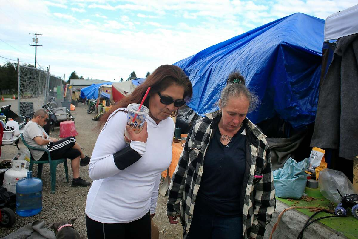 Betty Band (l to r) and Ellen Brown talk outside a tent at Last Chance Village on Wednesday, March 7, 2018, in Santa Rosa, Calif.