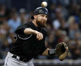 FILE - In this Sept. 23, 2017, file photo, Colorado Rockies catcher Jonathan Lucroy throws out San Diego Padres' Hunter Renfroe on an infield ground ball during the third inning of a baseball game in San Diego. The Oakland Athletics landed a new starting catcher, finalizing a $6.5 million, one-year contract with free agent Lucroy. The team announced the deal Monday, March 12, 2018. (AP Photo/Alex Gallardo, File)