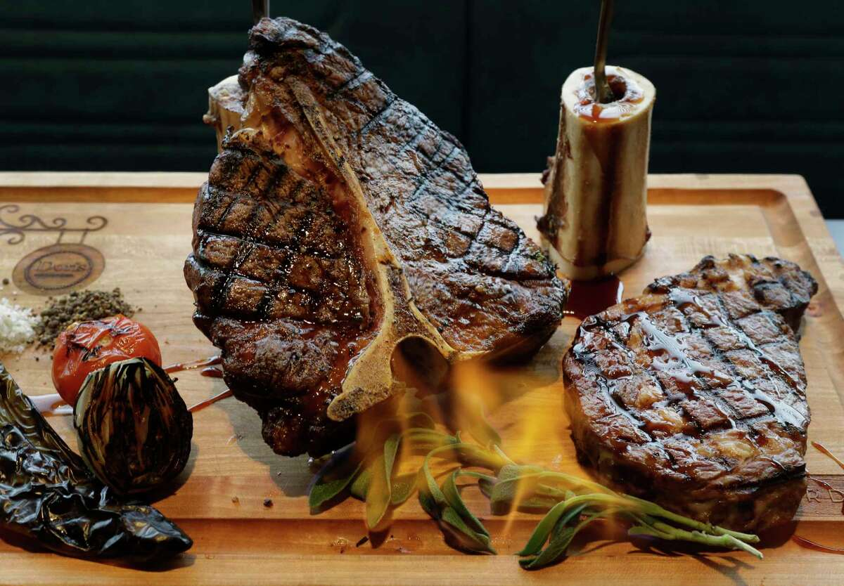 A meat board, complete with flaming sage, displays Doris Metropolitan's flavorful, tender and cooked-to-specification steaks.