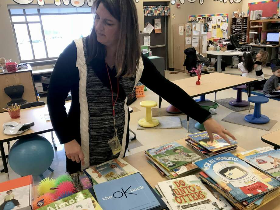 Tina DeBrock, a kindergarten teacher at Protsman Elementary School in Dyer, Ind. looks through some of the donated books on mental health wellness. (Jerry Davich/Post-Tribune/TNS) Photo: Jerry Davich/TNS