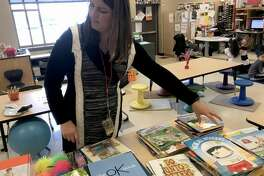 Tina DeBrock, a kindergarten teacher at Protsman Elementary School in Dyer, Ind. looks through some of the donated books on mental health wellness. (Jerry Davich/Post-Tribune/TNS)