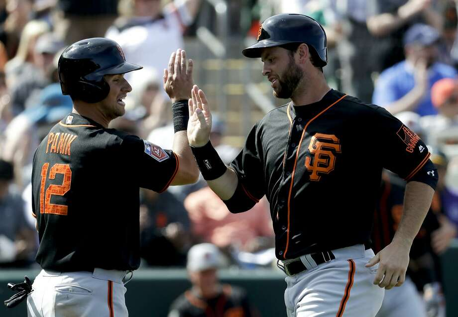 San Francisco Giants' Joe Panik, left, and Brandon Belt celebrate after scoring on Nick Hundley's three-RBI double during the fifth inning of a spring baseball game against the Oakland Athletics in Mesa, Ariz., Monday, March 12, 2018. Photo: Chris Carlson, Associated Press