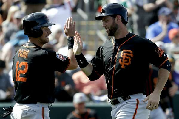 San Francisco Giants' Joe Panik, left, and Brandon Belt celebrate after scoring on Nick Hundley's three-RBI double during the fifth inning of a spring baseball game against the Oakland Athletics in Mesa, Ariz., Monday, March 12, 2018. (AP Photo/Chris Carlson)