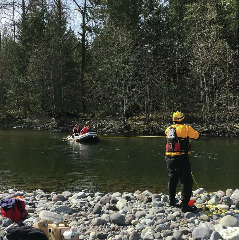Pierce County Sheriff's Office investigators cross the Carbon River after a man was killed and burned at a remote treehouse near Orting. Photo: Pierce County Sheriff's Office