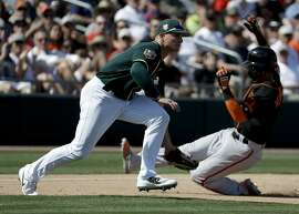 San Francisco Giants' Gorkys Hernandez, right, is safe at third past Oakland Athletics third baseman Matt Chapman on a double by Joe Panik during the fifth inning of a spring baseball game in Mesa, Ariz., Monday, March 12, 2018. (AP Photo/Chris Carlson)