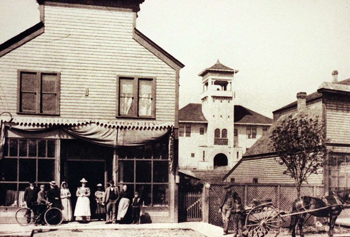 """1902. Helper Grocery,in Columbia City on the NW corner of Rainier and Ferdinand was built in 1893 by Alexander Helper, known to some as """"Uncle Alex."""" The Helper family (seen in front of the store) lived upstairs. Courtesy of RAINIER VALLEY HIST. SOC."""