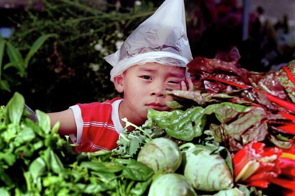 Jasing Chang, 4, of Monroe converted a plastic bag used to carry vegetables, fruit and flowers into a hat at his mother Lee Chang's booth at the Columbia City Farmer's Market on Wednesday.