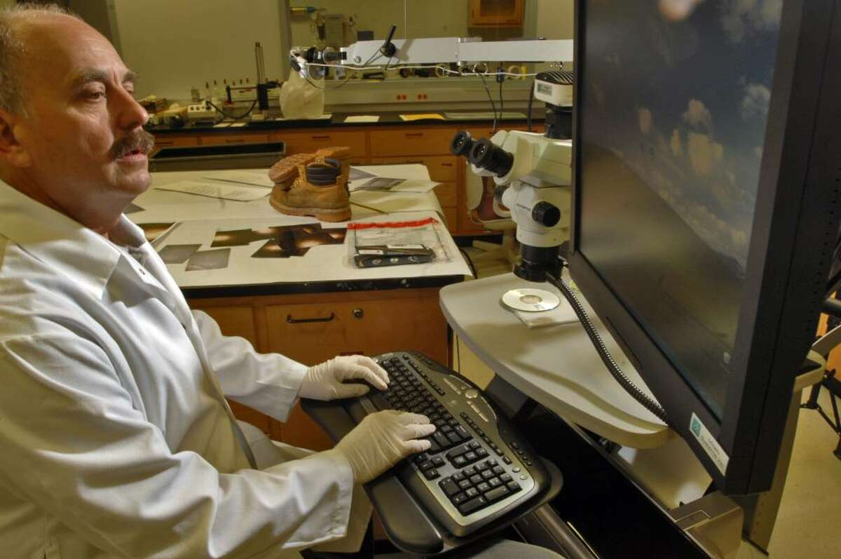 Forensic Scientist Garry L. Veeder examines evidence in the Trace Evidence Exam Room at the New York State Police Forensic Investigation Center in Albany. (File photo)