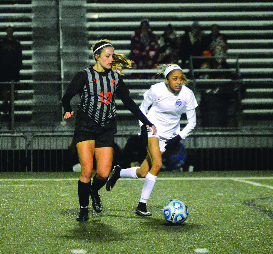 Edwardsville forward Sydni Stevens, left, prepares to play a ball down the field early in the second half of Monday's Metro Cup game against Belleville East inside the District 7 Sports Complex.