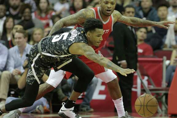 Second-year Spurs guard Dejounte Murray (5) loses control of the ball under Rockets forward P.J. Tucker's pressure. Murray is getting a crash course in the NBA thanks to coach Gregg Popovich.