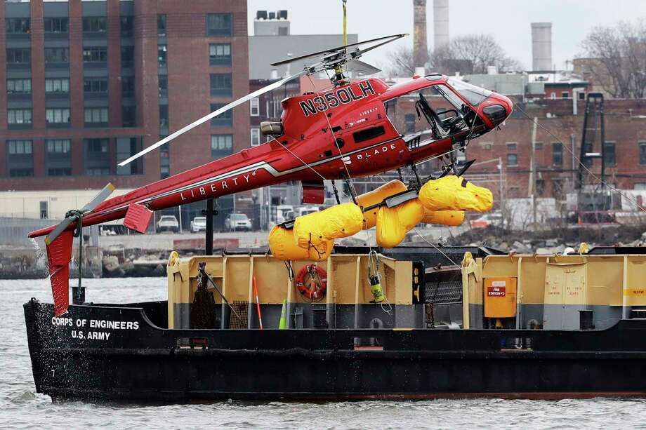 A helicopter is hoisted by crane from the East River onto a barge, Monday, March 12, 2018, in New York. The pilot was able to escape the Sunday night crash after the aircraft flipped upside down in the water killing several passengers, officials said. (AP Photo/Mark Lennihan) Photo: Mark Lennihan / Copyright 2018 The Associated Press. All rights reserved.