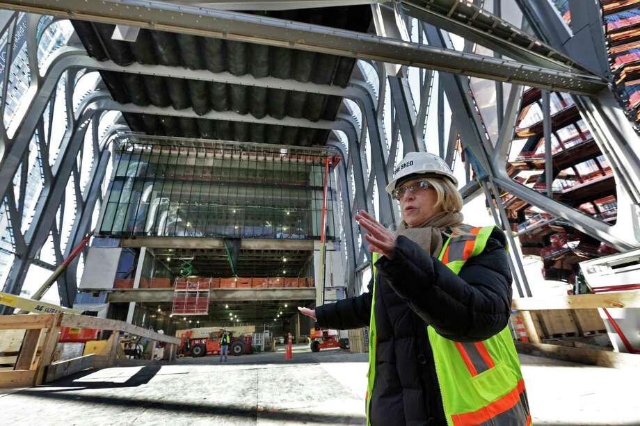 Laurie Beckelman, Associate Director of the Shed, describes ongoing construction in this Tuesday, March 6, 2018 photo, in New York. The building, in Manhattan's Hudson Yard's development, is a new arts space consisting of a stationary building with a a shell constructed around it that can move in a matter of minutes to cover the adjacent public plaza and create an additional 120-foot-high giant room. (AP Photo/Richard Drew) Photo: Richard Drew / AP