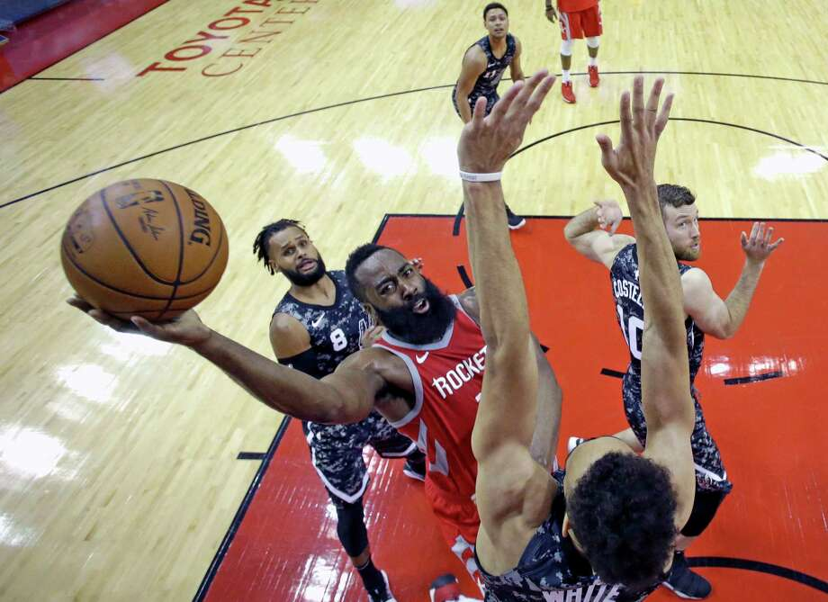 Houston Rockets' James Harden, center, shoots as San Antonio Spurs' Derrick White, bottom, defends during the second half of an NBA basketball game Monday, March 12, 2018, in Houston. (AP Photo/David J. Phillip) Photo: David J. Phillip / AP