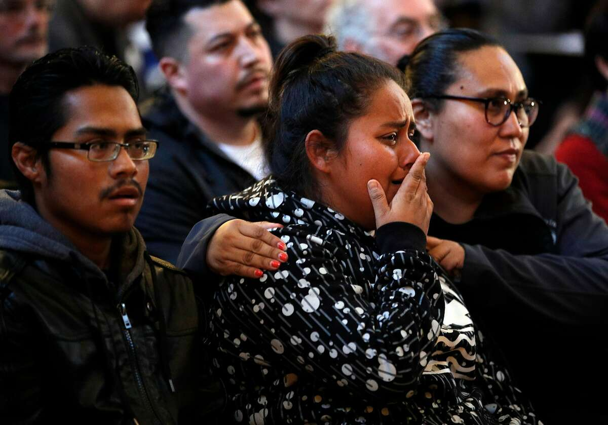 Patricia Torres, center, sister of Jesus Adolfo Delgado Duarte, reacts as body camera footage is shown during a townhall meeting with police to update the community on the investigation of the police involved shooting of Delgado Duarte at Cesar Chavez School in San Francisco, Calif., on Monday, March 12, 2018. On the left is Victor Torres, and on the right is family friend Susan Rojas.