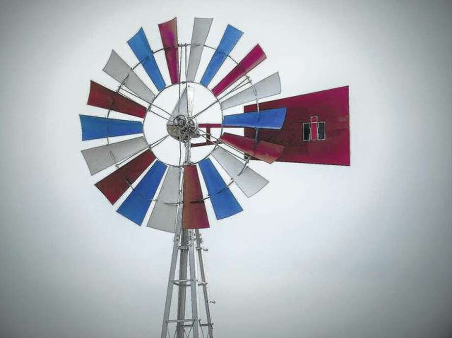 A patriotic red, white and blue windmill spins above Don Pence's Scott County farm. He has been farming in the county for more than six decades.