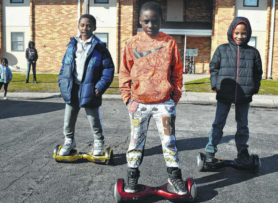 Lincoln Elementary School students Christopher Hill (from left), 9, Kavion Baker, 8, and Ka'rell Rattler, 8, ride their hoverboards after school Monday on Walnut Street. Photo: Nick Draper | Journal-Courier