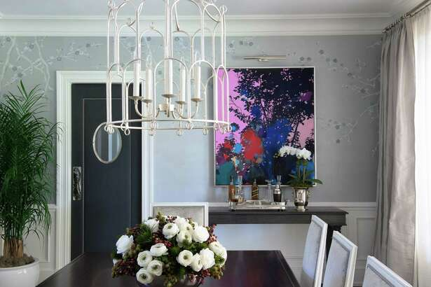 In a classic Georgian estate in Greenwich, contemporary wallpaper, a unique chandelier, a colorful pop of abstract art and an uncluttered approach bring a modern feel to a traditional dining room designed by Christina Roughan.