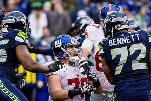 Giants player Weston Richburg, center, reacts to getting a finger in the eye from Seahawks player Michael Bennett, right, during the second half of a game Sunday, November 9, 2014, at CenturyLink Field in Seattle, Washington. The Seahawks beat the Giants 38-17. (Jordan Stead, seattlepi.com)