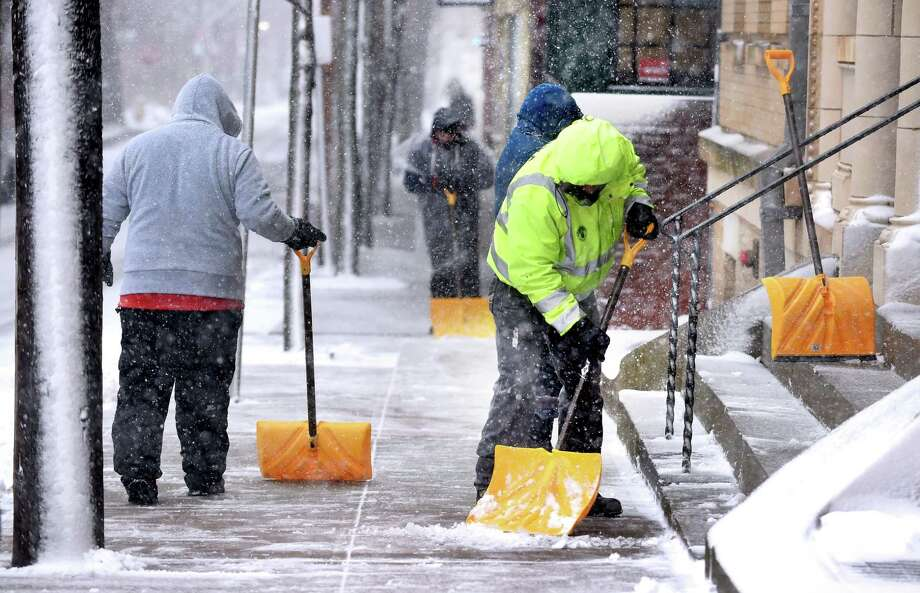 A crew of shovelers clears the snow on a sidewalk on Wall St. in New Haven on March 13, 2018. Photo: Arnold Gold / Hearst Connecticut Media / New Haven Register