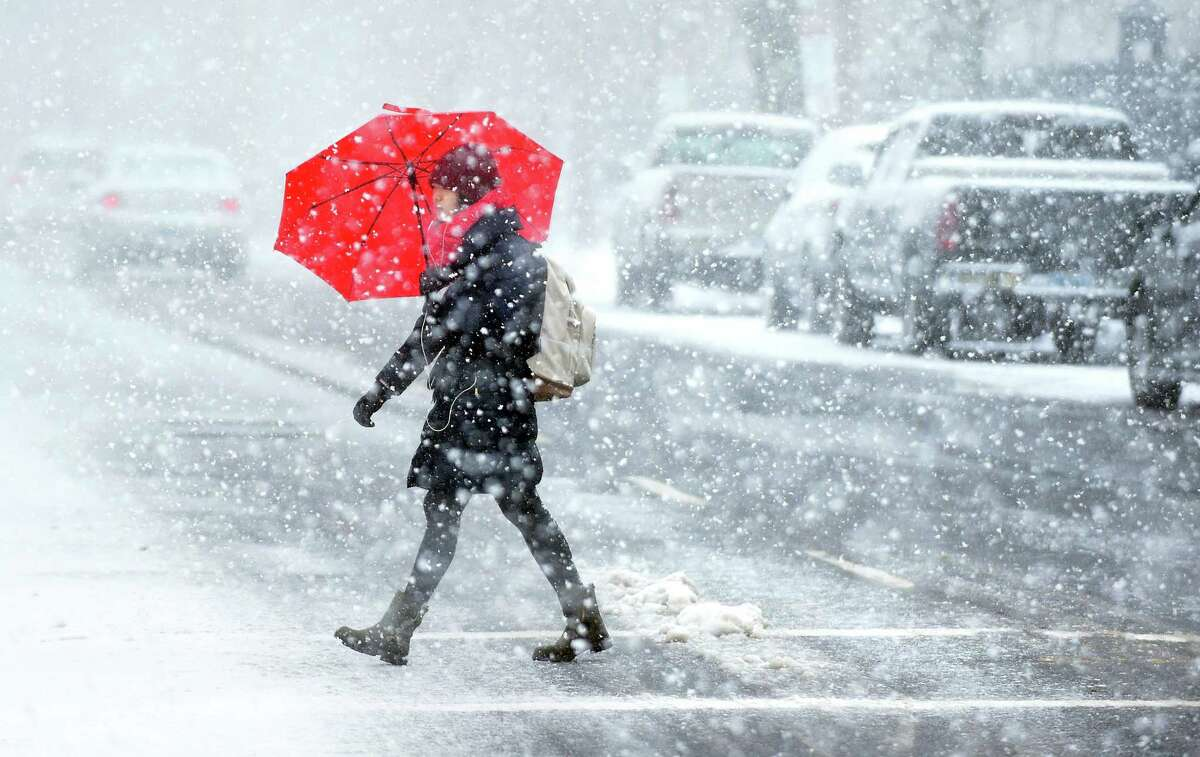 A woman shields herself from the wind and snow crossing College St. in New Haven on March 13, 2018.