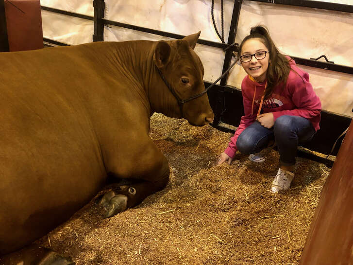 Aven Horn poses with her 1,359-pound steer named Rudy one day before the junior market steer show.