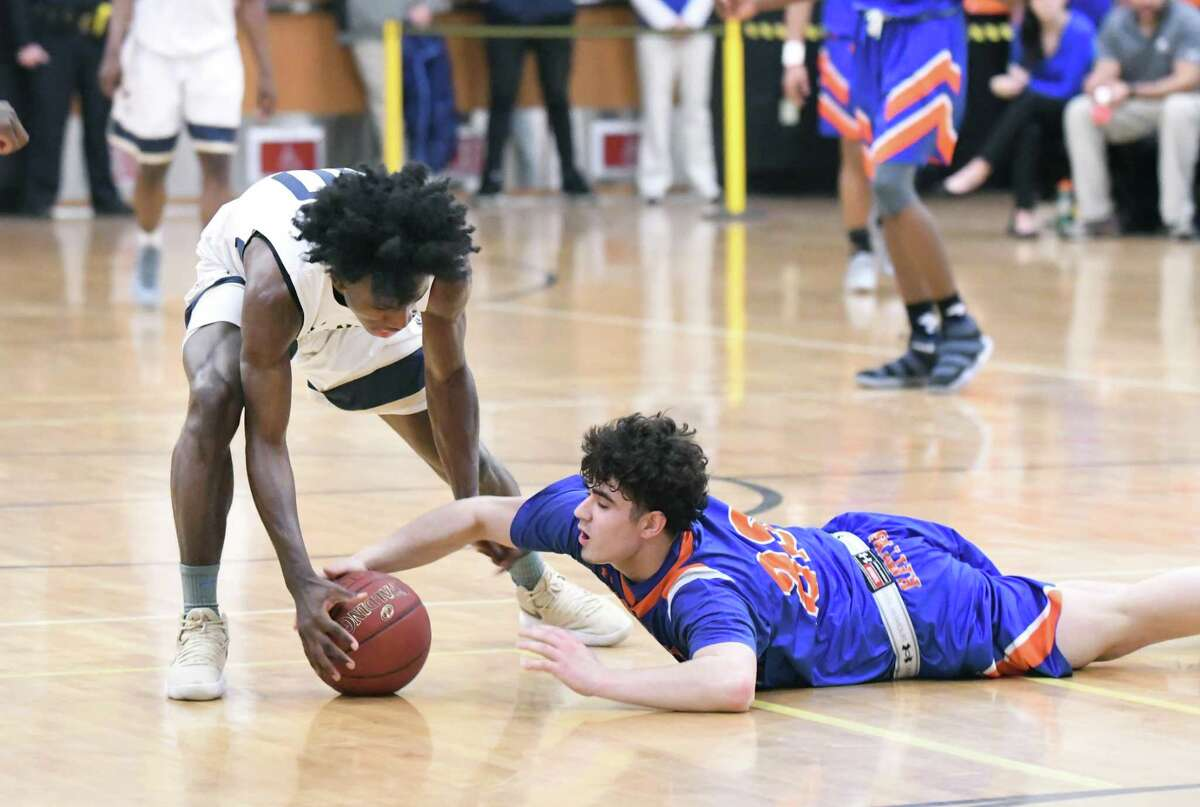 Notre Dame?'s Woodley Monnexant, left, and Danbury?'s Cameron Snow scramble for a loose ball during the Division I boys basketball quarterfinals between Danbury and Notre Dame-Fairfield at Trumbull High, March 12, 2018.