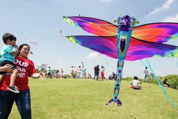 Jaleigh Gonzales holds Brayden Mairui-Rhodes to launch a kite during the Hermann Park Conservancy Kite Festival at Hermann Park on Sunday, March 26, 2017, in Houston. ( Brett Coomer / Houston Chronicle )