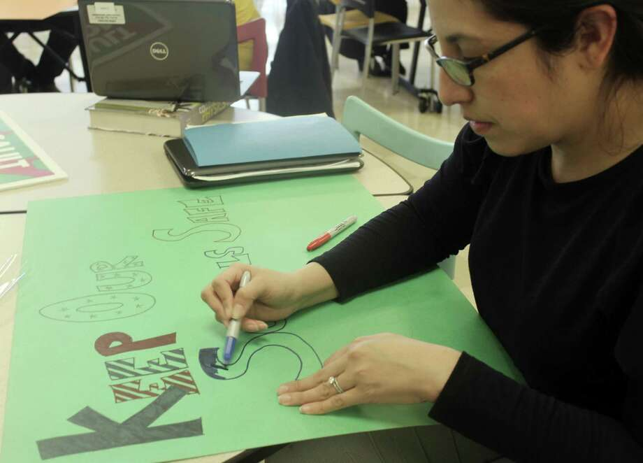 "Maria DeAntonis, a guidance counselor at the Academy of Information Technology and Engineering in Stamford, Conn., works on a sign after school on March 12, 2018 for a teacher ""walk-in"" planned in conjunction with the student walkout on March 14. The goal of the walk-in is to push Congress to take action to make schools safer. Photo: Erin Kayata / Hearst Connecticut Media / Stamford Advocate"