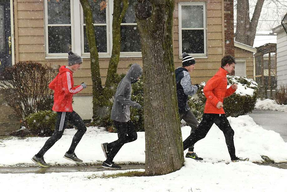 Members of the Albany Academy boys cross-country team run down a sidewalk along Academy Road during a snow storm on Tuesday, March 13, 2018 in Albany, N.Y. (Lori Van Buren/Times Union) Photo: Lori Van Buren, Albany Times Union / 20043196A