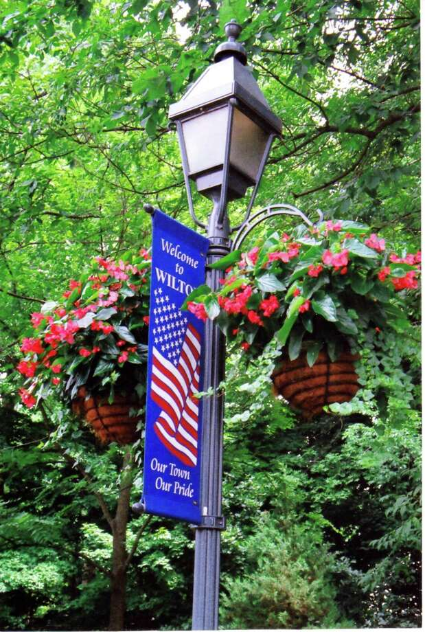 A lamppost in Wilton Center is decorated by baskets filled with flowers of vibrant colors. Photo: Contributed Photo