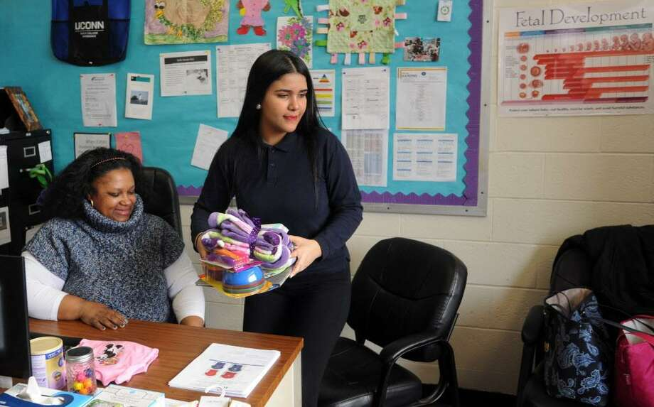 Moyry Ramos, right, a junior at Harding High School, packs up some items given to her after meeting with Natisha Vidal, a teen pregnancy social worker at Harding High School in Bridgeport, Conn. on Friday, March 9, 2018. Ramos plans to enroll her 2-year-old daughter in the  Early Learning Center day care planned at the new Harding High School when it opens next fall. Photo: Cathy Zuraw / Hearst Connecticut Media / Connecticut Post