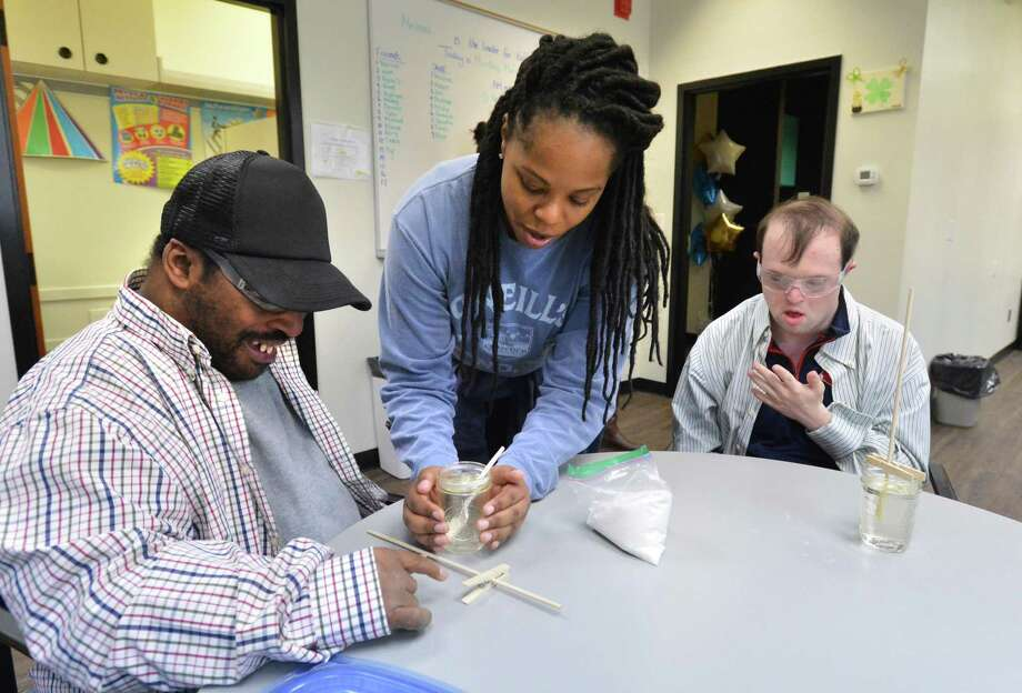 Neldine Jolicour, Day Program Assistant Manager, helps with more sugar for Darrick H. while making rock candy during a program at Ability Beyond on Monday March 12, 2018  a nonprofit that supports individuals with disabilities in Norwalk Conn. Photo: Alex Von Kleydorff / Hearst Connecticut Media / Norwalk Hour