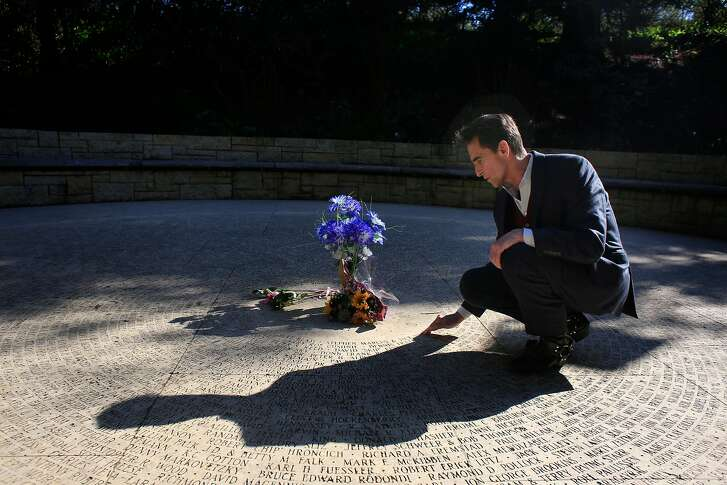 Mark Leno looks at familiar names as he kneels next to the Cirlcle of Friends at the AIDS Memorial Grove on Wednesday, February 21, 2018.