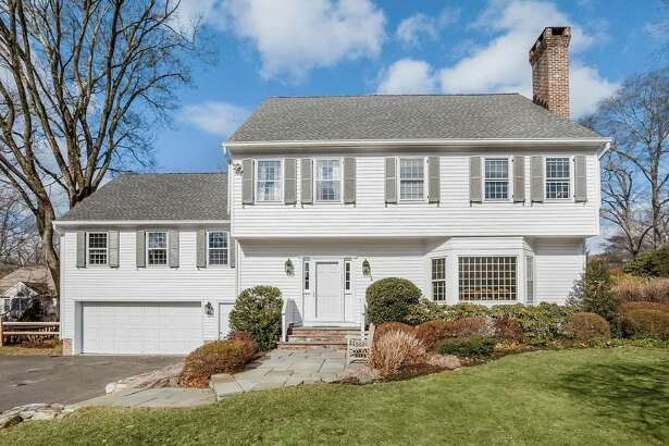 The pale gray Garrison colonial at 9 Colony Road is only steps away from Woodland Park Nature Preserve.
