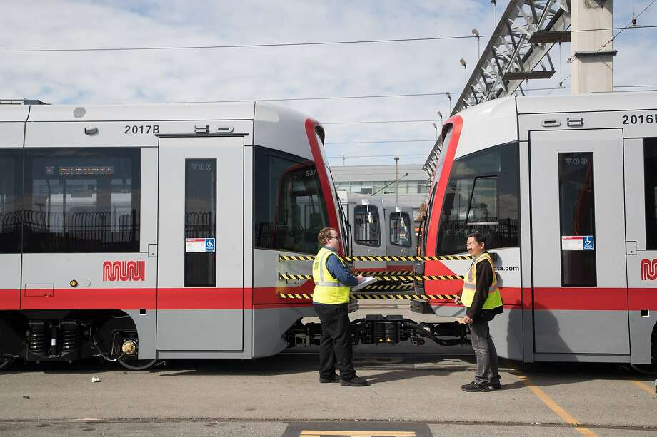 Lucas Smith and Doug Lee talk near one of the new Muni Metro light-rail cars. Photo: Paul Kuroda, Special To The Chronicle