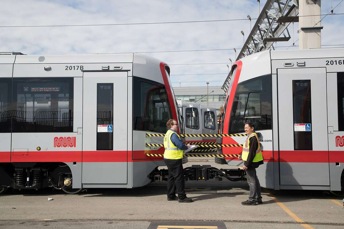 Lucas Smith and Doug Lee talk near one of the new Muni Metro light rail cars on Monday, March 12, 2018 in San Francisco, CA