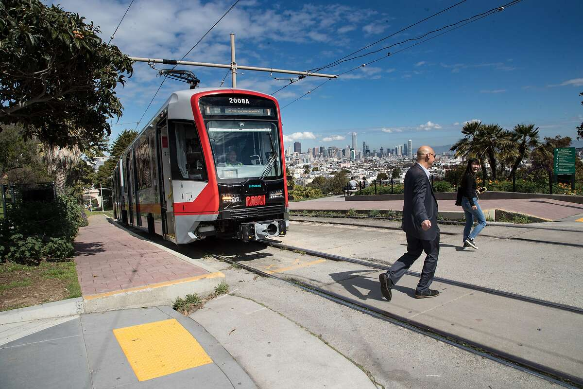 Reid Carter and Youjin Jung leave a new Muni Metro light rail cars on Monday, March 12, 2018 in San Francisco, CA