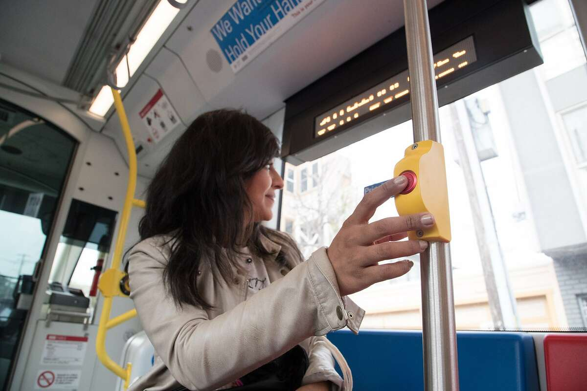 Gina Gonzales presses a stop button on a new Muni Metro light rail car on Monday, March 12, 2018 in San Francisco, CA