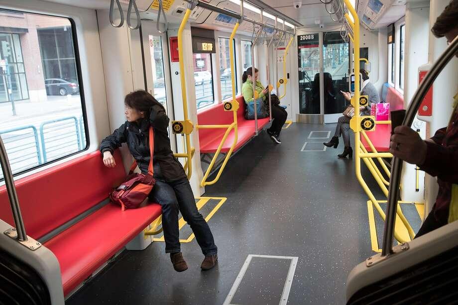 Passenger Helen Yan rides one of Muni Metro's new light-rail cars. Photo: Paul Kuroda, Special To The Chronicle